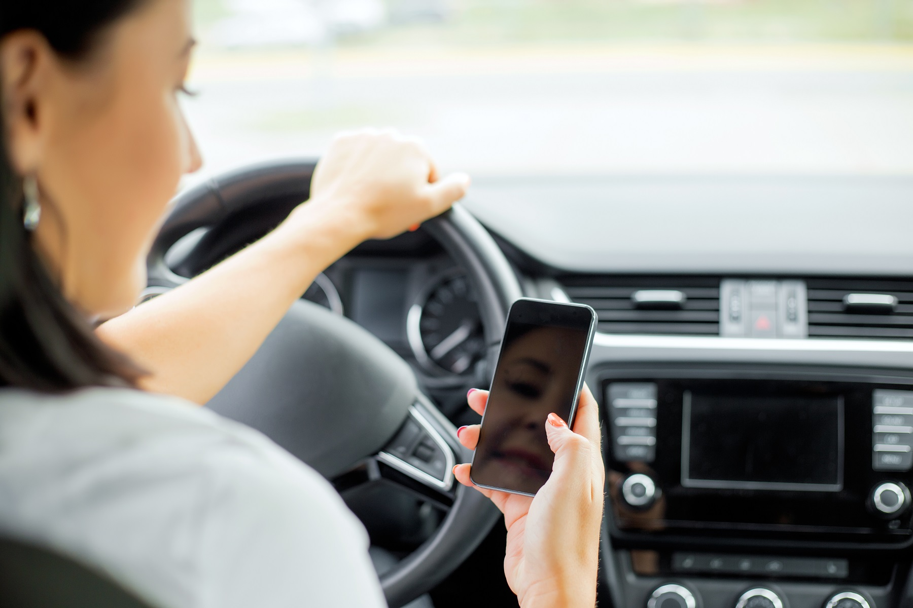 female driver using her smartphone while driving